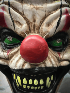 Photo of a scary clown with a red nose.
