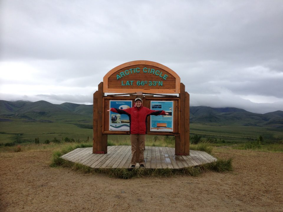 Pausing from swatting away mosquitoes to take a photo at the Arctic Circle sign