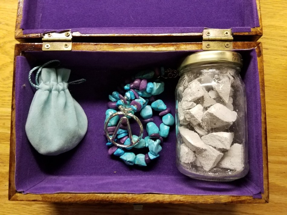 A wooden box is open on top of a wooden table. The inside is lined with purple velvet. To the left is a light blue bag, to the center a necklace of natural looking turquoise and purple beads. To the right is a glass mason jar filled with grey stone and sand.