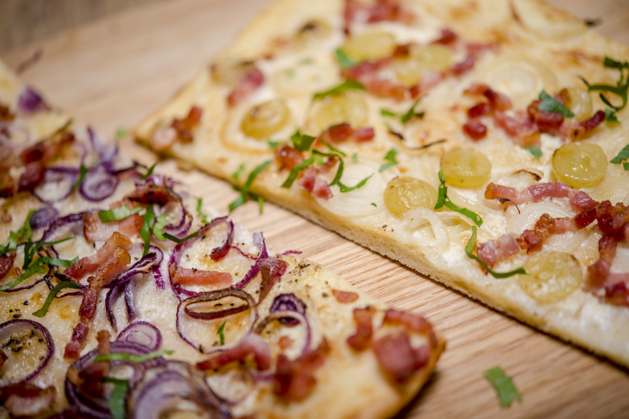 """tarte flambée - a kind of """"French pizza"""" from Alsace made from a very thin layer of pastry topped with sour cream, chopped onions, grapes and bacon"""