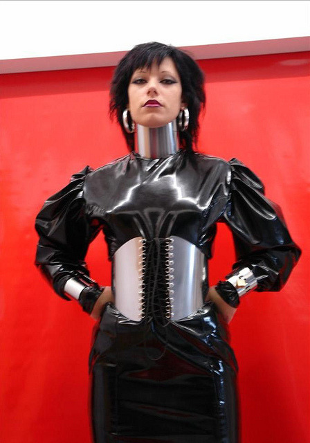 """What do you mean, we don't have any neck belts? We got a domme here who's paying for a photoshoot, we can't just have her standing there, can we? Here's $20; head down to the hardware store at the corner and pick up something shiny for her to wear,..."