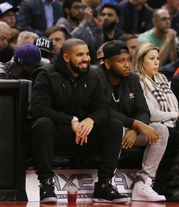 TORONTO, ON - DECEMBER 05:  Rapper Drake (L) looks on from his courtside seat during an NBA game between the Golden State Warriors and the Toronto Raptors at the Air Canada Centre on December 05, 2015 in Toronto, Ontario, Canada.  NOTE TO USER: User expressly acknowledges and agrees that, by downloading and or using this photograph, User is consenting to the terms and conditions of the Getty Images License Agreement.  (Photo by Vaughn Ridley/Getty Images)