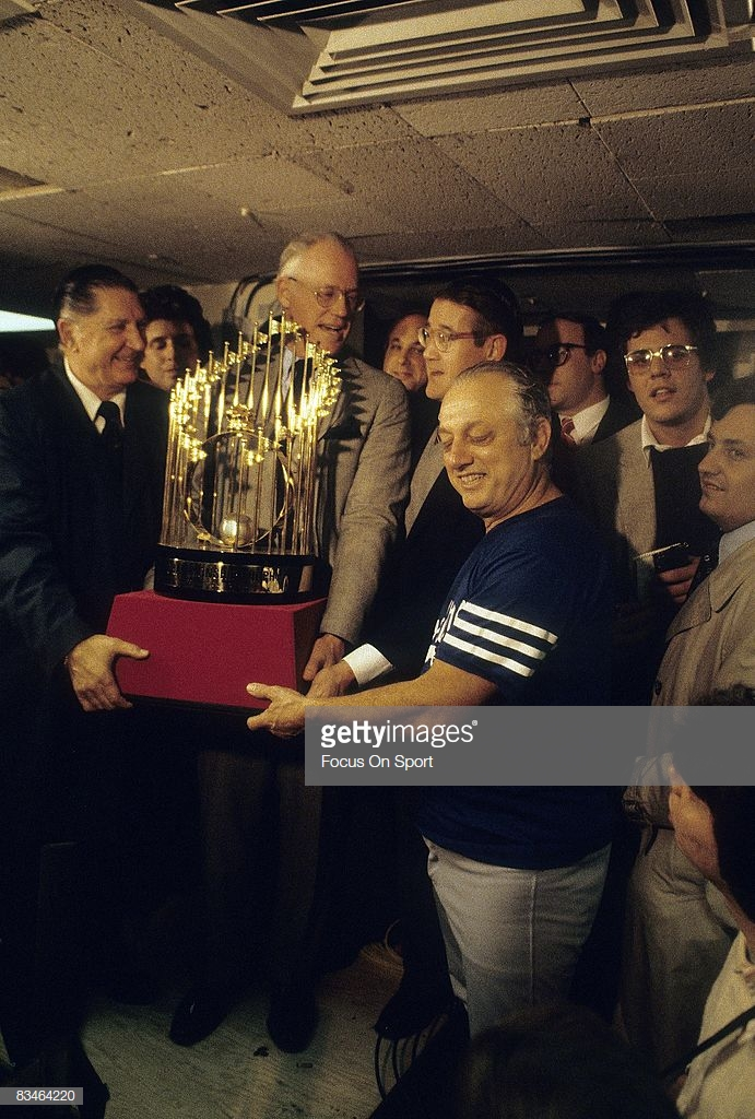BRONX, NY - OCTOBER 28, 1981: Manager Tommy Lasorda, right has his hands on the world series trophy while Commissioner of baseball Bowie Kuhn, center presents it to the team in the locker room after the Dodgers defeated the New York Yankee in game six  of  the World Series October 28, 1981 at Yankee Stadium in Bronx, New York. The Dodgers won the series 4-2. Lasorda managed the Dodgers from 1976-96. (Photo by Focus on Sport/Getty Images)