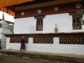 Old lady at the prayer wheels