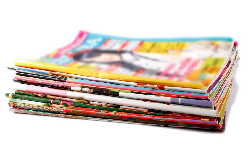 12945702 - a stack of old colored magazines on white