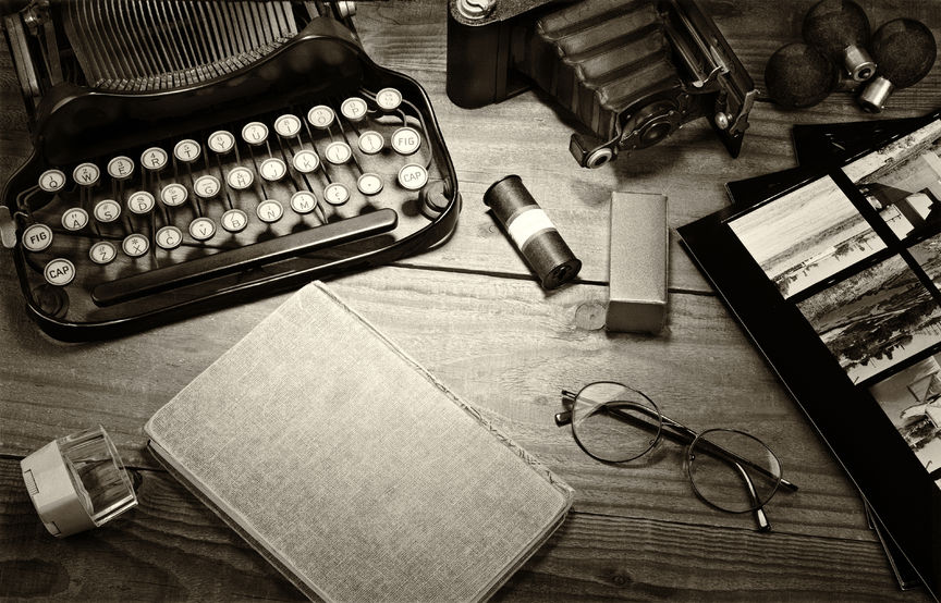 36499263 - closeup of a vintage photography still life with typewriter, folding camera, loupe, roll film, flash bulbs, contact prints and book on a wood table. black and white toned image for a vintage feel.