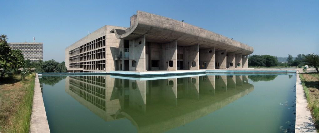 """El Parlamento de Chandigarh forma parte del Complejo del Capitolio que comprende tres edificios: la Asamblea Legislativa, el Edificio del Secretariado y el Palacio de Justicia. Tras la partición del Punyab, en 1947 después de la independencia de la India, el dividido Punyab necesitaba una nueva capital, por lo que el primer ministro de la India, Jawaharlal Nehru, encargó a Le Corbusier, que construyera una nueva ciudad, Chandigarh. El encargo se definía como una ciudad """"no condicionada por las tradiciones del pasado, un símbolo de la fe de la nación en el futuro"""". Posteriormente, Le Corbusier y su equipo construyeron no sólo un gran palacio de asamblea y un palacio de justicia, sino todos los grandes edificios de la ciudad."""