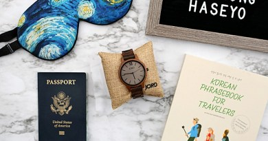 a wooden Jord watch, passport, face mask, and Korean travel guide on a table