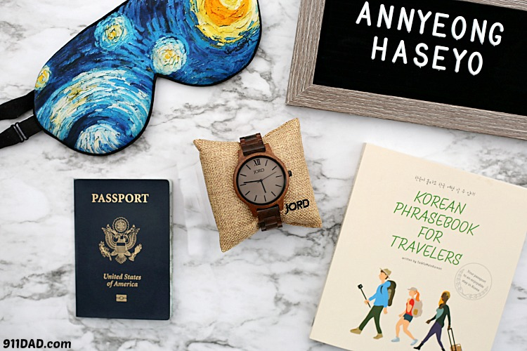 travel accessories for men: a wooden Jord watch, passport, face mask, and Korean travel guide on a table