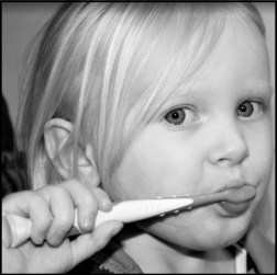 Photo of young girl brushing her teeth