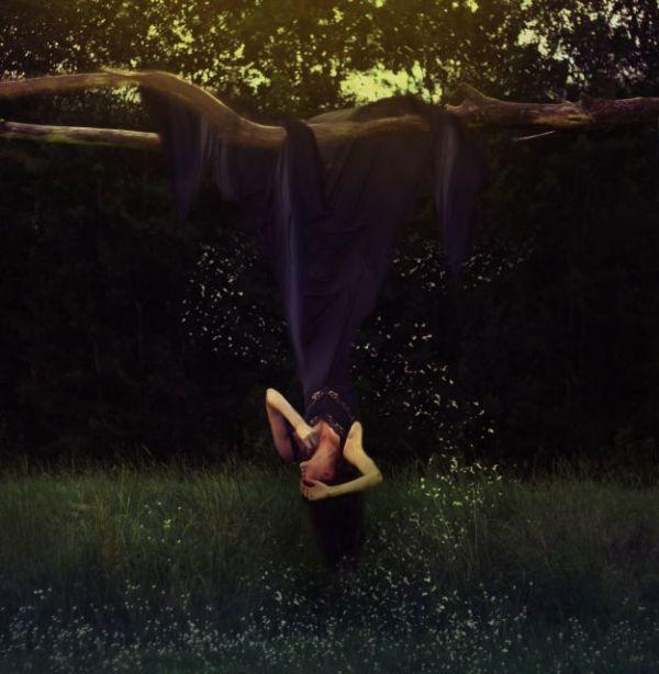 Фото Девушка висит вниз головой, зацепившись платьем за ...