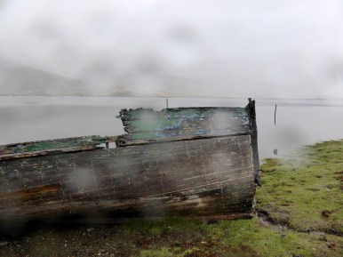 ruined boat on misty lochside
