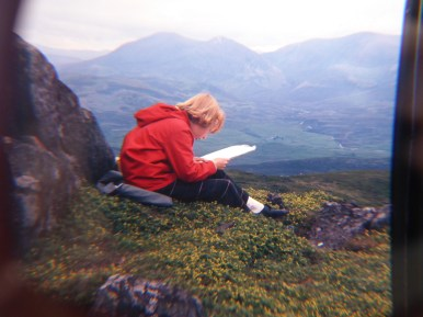 girl on hillside in red anorak reading map