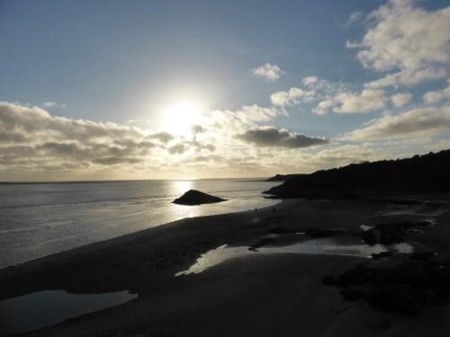 blue sky, silver sea, black beach
