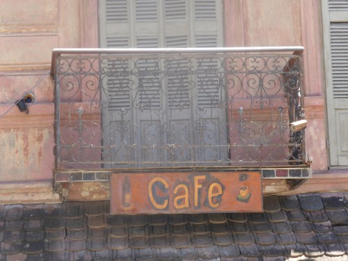 hand-painted cafe sign and iron balcony