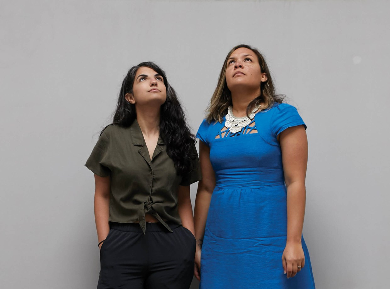 Two women looking up against a grey background.