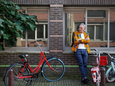 Erik Kessels in a fun yellow jacket posing by some bikes.