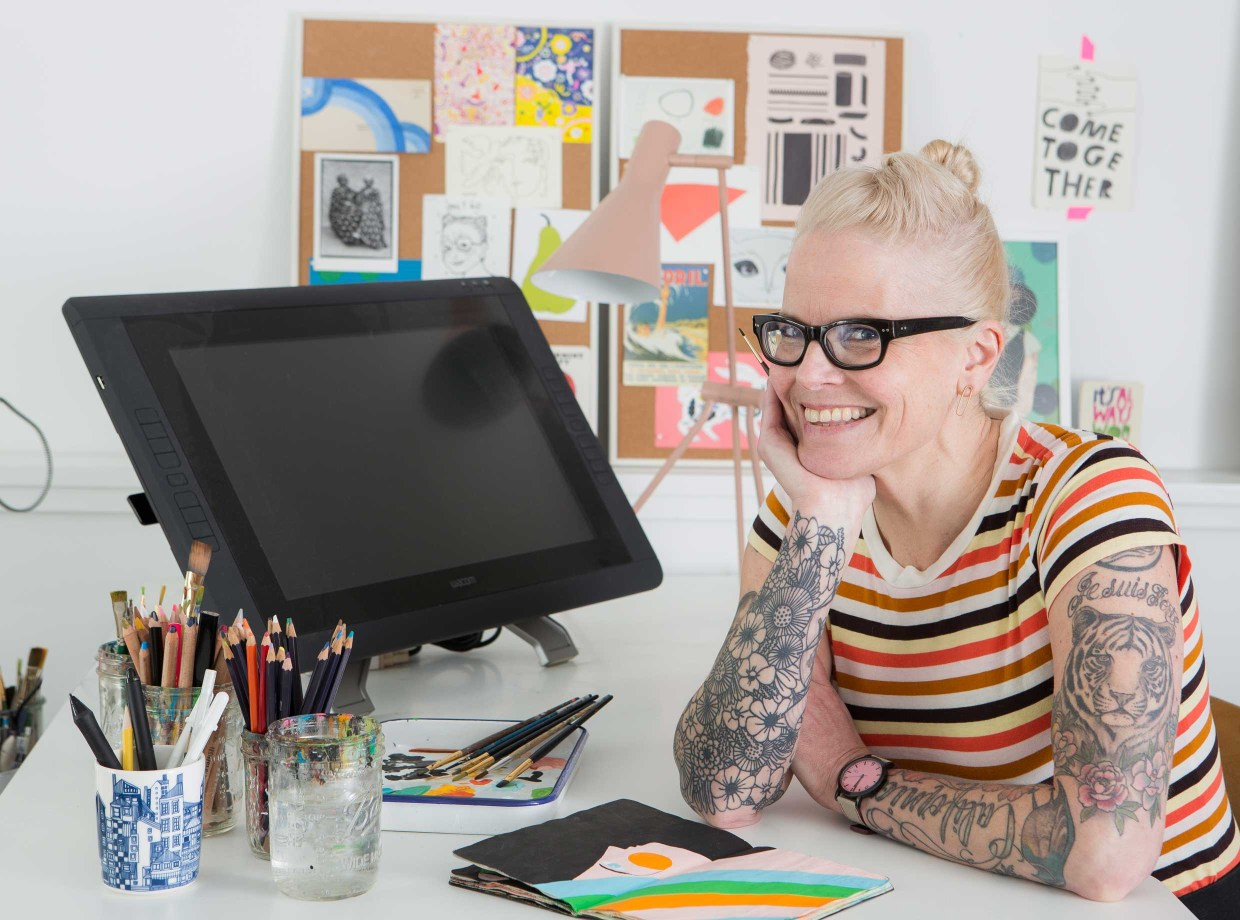 A woman with white-blonde hair, tattoos and glasses smiles in front of her digital drawing screen