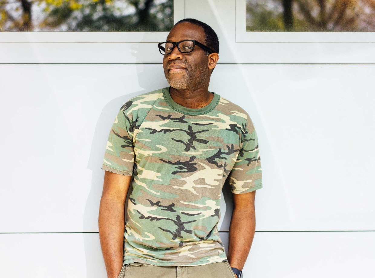 A man in camouflage shirt and glasses before a white garage door
