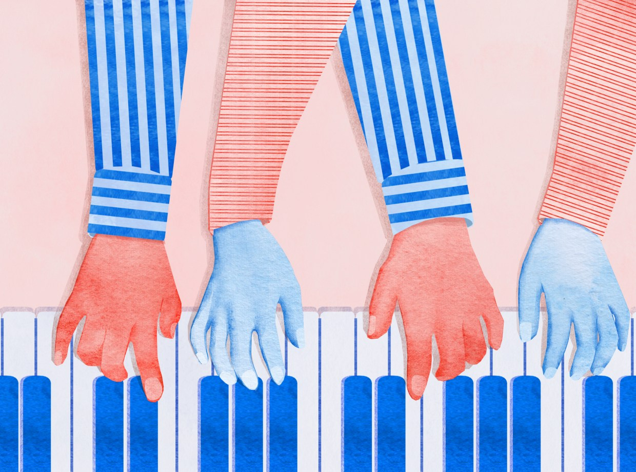 Two pairs of hands playing a piano.