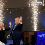 Israeli Prime Minister Benjamin Netanyahu and his wife Sara react as they stand on stage following the announcement of exit polls in Israel's parliamentary election at the party headquarters in Tel Aviv, Israel April 10, 2019. REUTERS/Ronen Zvulun