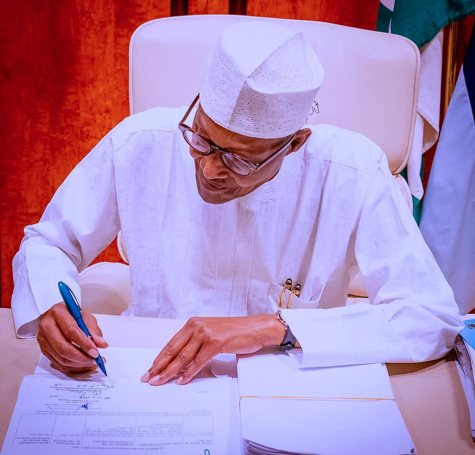 President Buhari Signing a document -