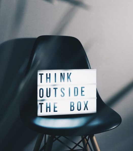 "sign with words ""think outside the box"" on a black chair"