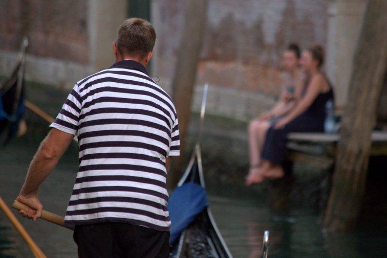A gondolier passing tourists