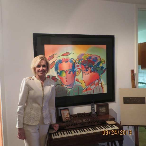 Joyce Selander in front of her Peter Max painting and 1867 Melodeon