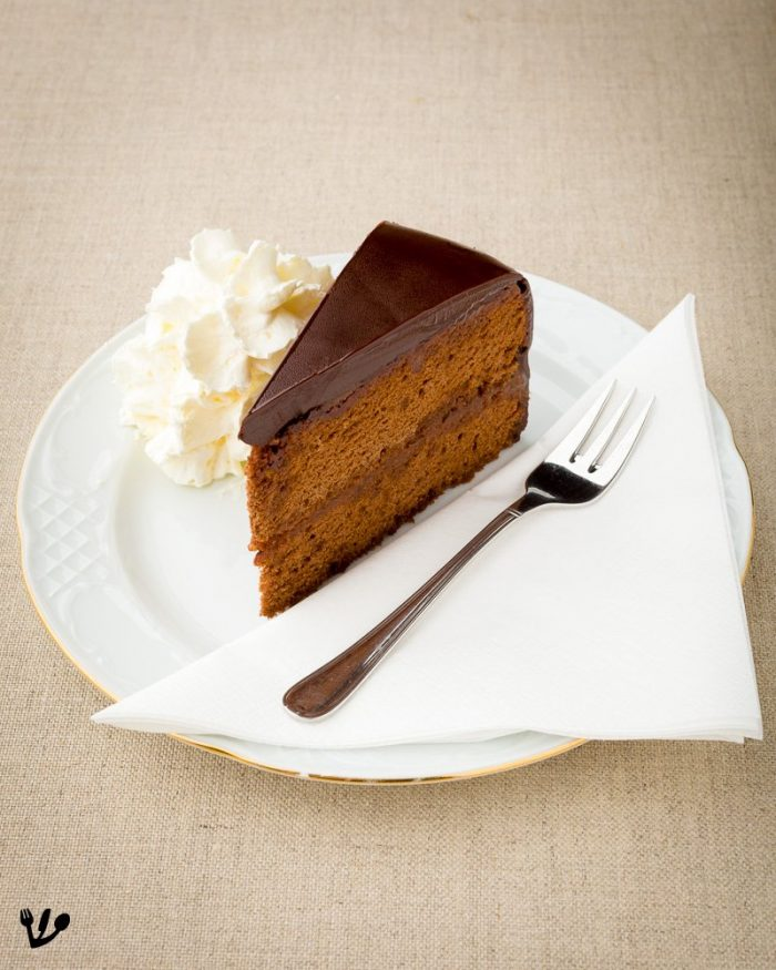 "A slice of elegant homemade Sachertorte à la Café Sabarsky at Ronald Lauder's Neue Galerie in New York. Always served with ""Schlag"", sweetened whipped cream, which literally translates to ""blow"". Each and every bite should be accompanied by it."
