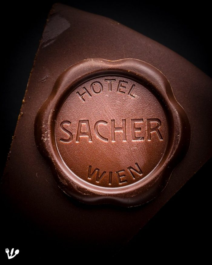 "Hotel Sacher seal on a so-called ""original"" Sachertorte. ""[Salvador] Dalí recalls [...] spending afternoons walking haphazardly through the streets of Vienna, eating chocolate tarts, which, he claims, possessed a bitterness accentuated by the meeting [with Sigmund Freud] that never took place. 'In the evenings,' he recalls, 'I held long and exhaustive imaginary conversations with Freud; he came home with me once and stayed all night clinging to the curtains of my room in the Hotel Sacher.'"" (Mark Edmundson, The Death of Sigmund Freud. Fascism, Psychoanalysis and the Rise of Fundamentalism, pp.166-167.)"