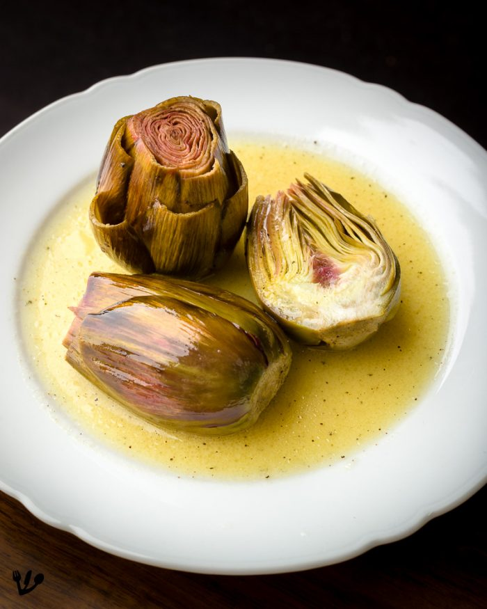 Artichokes confit are also beautiful when halved. They are delicious with a mayonnaise or a vinaigrette made out of the cooking oil. If you decide to leave them whole, you will have to chew on each and every leaf, scraping the meaty part off the petals between your teeth.