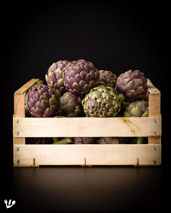 """<em>Artichokes are so beautiful! A crate of organiccarciofi""""romanesci"""", aka """"mammole"""" artichokes imported directly from neighboring Italy and bought on Vienna's Karmelitermarkt market. The market is situated on the so-called """"</em><a href=""""https://JewishVienneseFood.com/mazzesinsel-sebestyen-fiumei/""""><em><u>Mazzesinsel</u></em></a><em>"""" (""""matzo island""""), a traditionally Jewish neighborhood, which is adjacent to old town center and is sandwiched between the Danube river and its canal.</em>"""