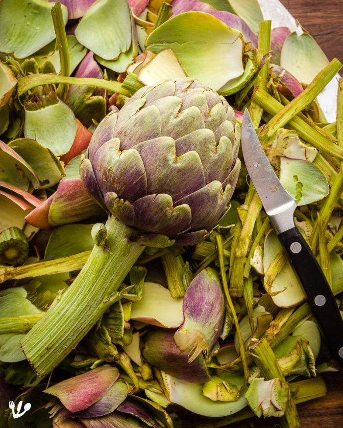 Cleaning artichokes for carciofi alla romana usually makes a big mess. You should make sure to wear gloves to avoid staining your fingers with the oxidizing artichokes. A very sharp knife, more precisely a peeling or turning knife, is ideal. When you're finished, make sure not to discard the leaves or stem. Instead, use them as the ingredients for the purée (see recipes below) or stock for a delicious artichoke risotto!
