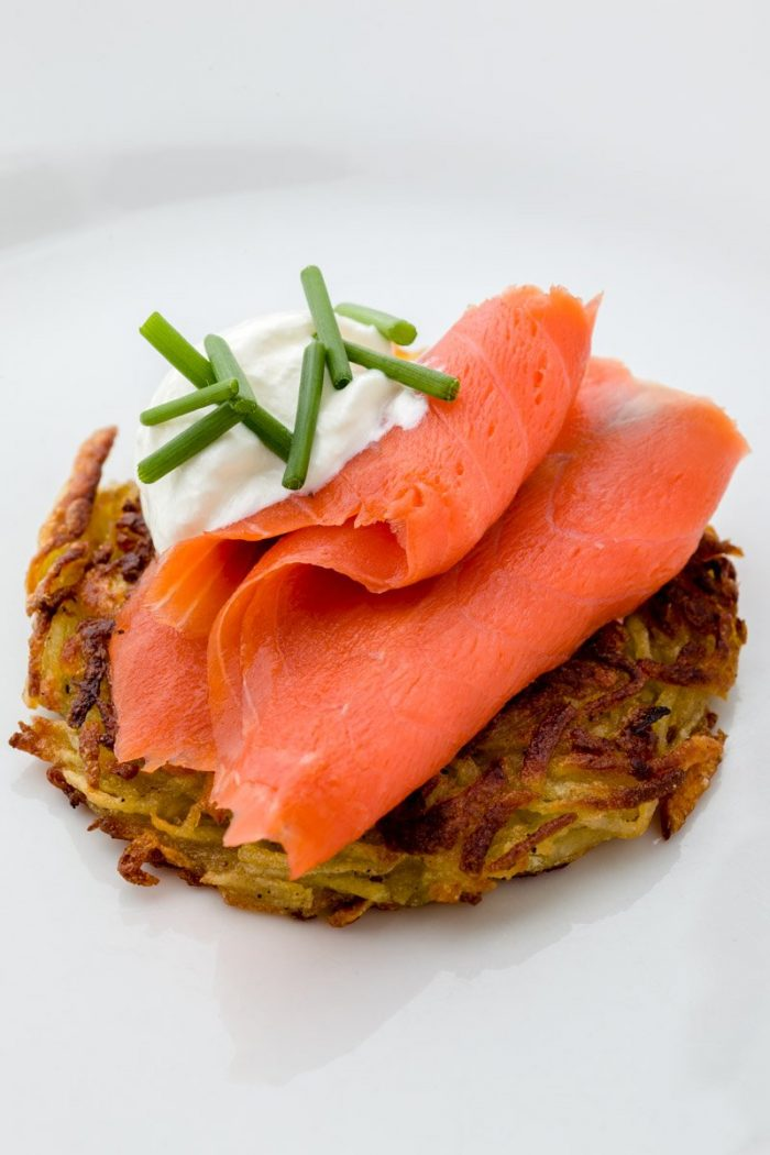 A perfect latketopped with smoked salmon, sour cream and chives. Gravlax is a very good alternative. Here I combined this lowly potato fritter with expensive and delicate line-caught, cold-smoked wild salmon. But I prefer the bold flavored salty lox in this combo.