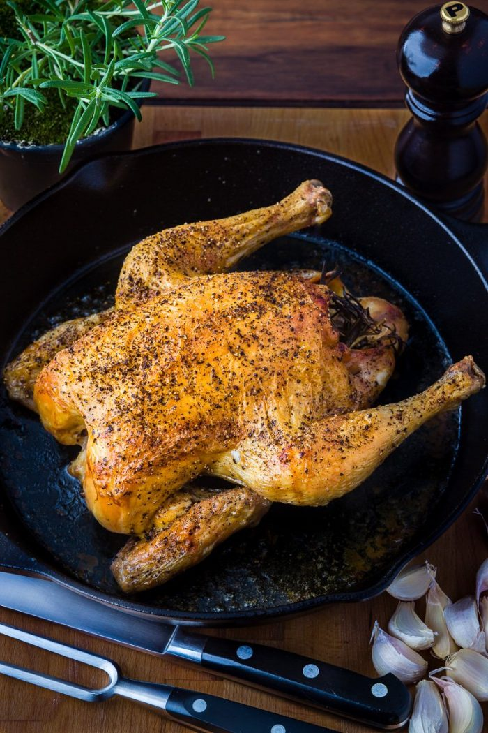 Perfectwhole roast chicken in cast-iron skillet with salt and pepper, rosemary, garlic and olive oil.