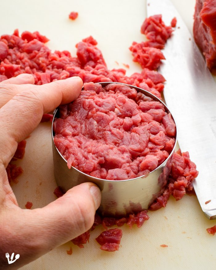 It is best to chill all equipment necessary for the preparation of the tartare. Use a pastry ring to form very meticulously exact round patties of meat.