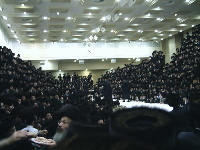 In the foreground a Hasid distributes pieces of gefilte fish out of a jar to the Hasidim gathered around the Belzer rebbe's tish celebration. (Photo: Daniel575 for Commons Wikimedia)