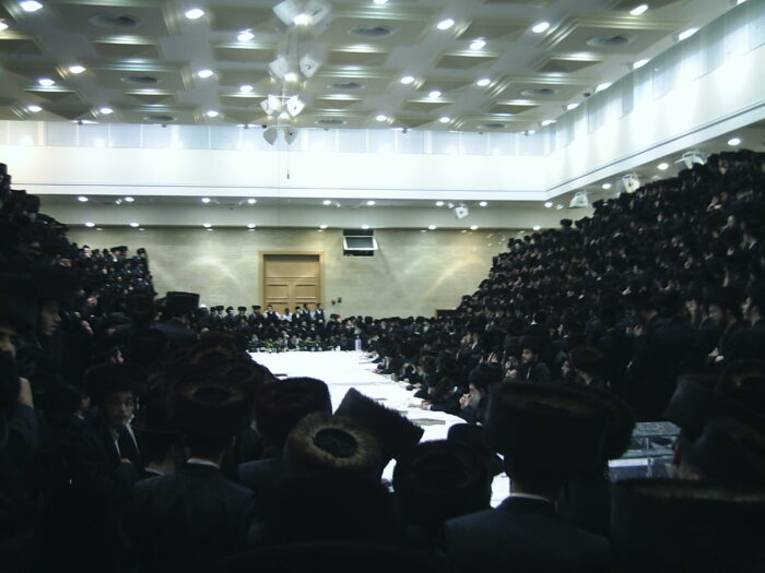 """Hasidim gathered around the rebbe at a """"tish"""" (Yiddish for """"table"""") of the Belzer Rebbe in Jerusalem. (Photo: Daniel575 for Commons Wikimedia)"""