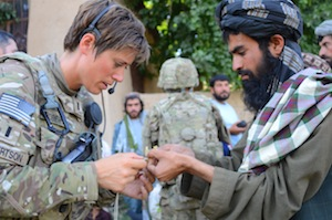 An Afghan farmer shows 1st Lt. Tara Robertson, a member of the Minnesota Army National Guard serving with the Zabul Agribusiness Development Team, a diseased plant during a shura conducted while on a partnered patrol with Afghan Uniformed Policemen, Afghan National Army soldiers and US Soldiers from C Troop, 1st Squadron, 14th Cavalry Regiment, 615th Civil Affairs Team and Zabul Agribusiness Development Team of the Mizan District in southern Afghanistan.