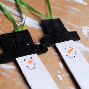 Step 6: Draw a snowman face. Dots for eyes, dot mouth or smiley mouth and orange triangle for the nose.