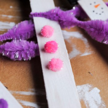 Step 8: Use glue dots to place 3 pom poms or 3 buttons below the scarf.