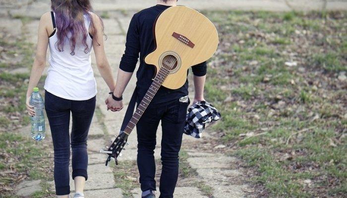 Парень с гитарой гуляет с девушкой
