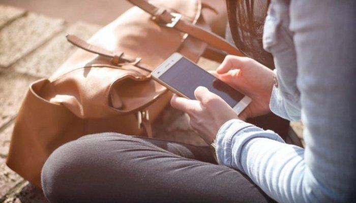 Девушка пишет в телефоне