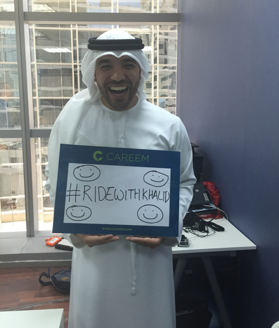 Khalid Al Ameri holding his #RideWithKhalid sign at Careem offices