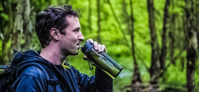 lifestraw_go_2-stage_outdoor_7-man-hiking-walking-forest-drinking-water-puddle-stream-river-purification