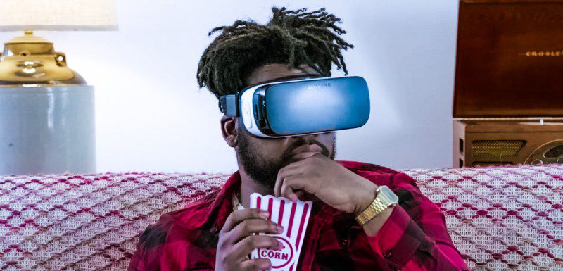 Man Sitting Home Couch Watching Movie Eating Popcorn VR Headset Samsung Gear On Hulu