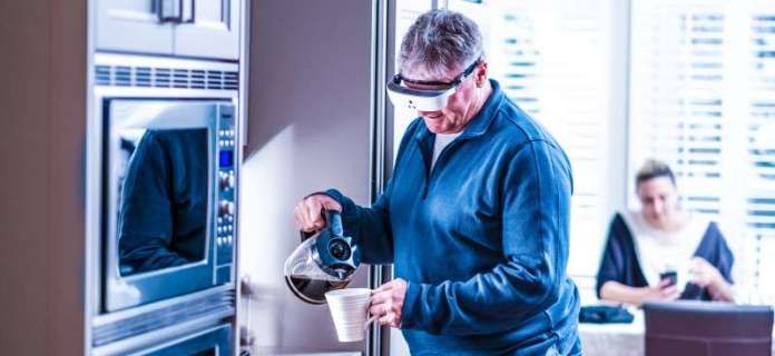 eSight Wearable Legally Blind Low Vision Man Doing Chores Home Pouring Coffee Normally Smiling Happy User Case Lifestyle Photo