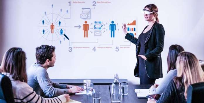 eSight Wearable Legally Blind Low Vision Work Business Professional Woman Holding Presentation Meeting Room Deck Demo