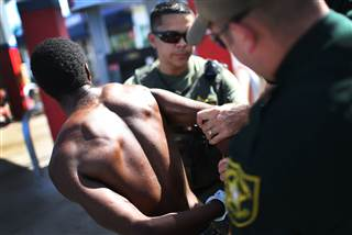 Image: Sgt. Ozzy Tianga and a deputy handcuff a man suspected of being under the influence of flakka